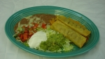 Taquitos Mexicanos - Two taquitos deep-fried to a golden brown. Topped with lettuce, tomatoes and guacamole. Served with rice and beans.